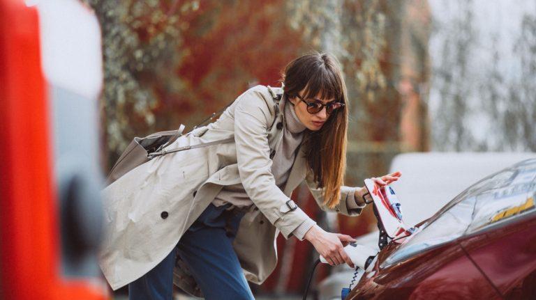 Femme en train de brancher sa voiture électrique à une borne de recharge