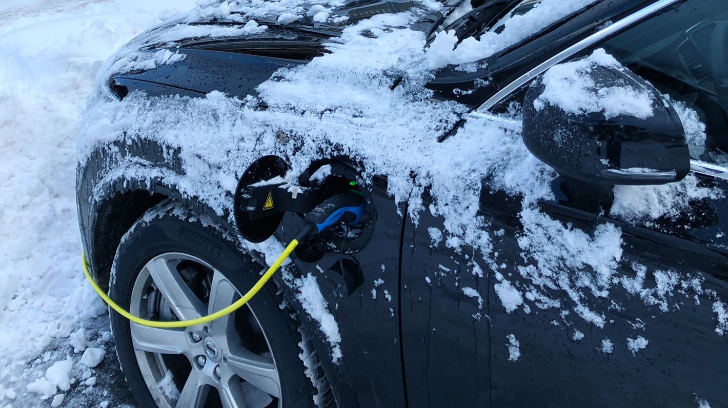 Aufladen eines verschneiten Elektroautos im Winter