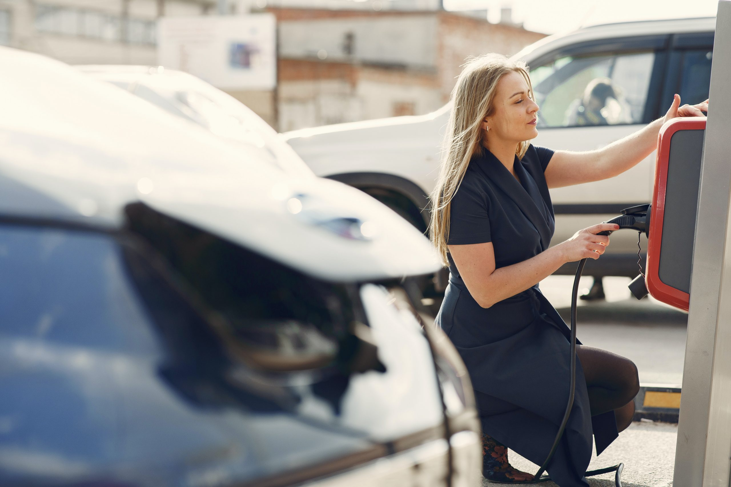 Femme en train de brancher son véhicule électrique à une borne de recharge en entreprise